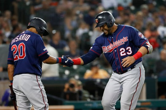 Minnesota Twins' Nelson Cruz (23) celebrates his solo home run with Eddie Rosario (20) during the eighth inning.