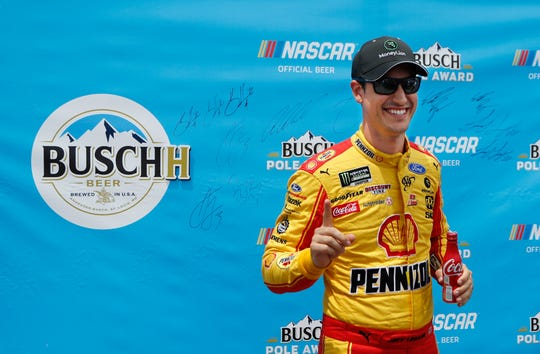 Joey Logano signals No. 1 during the pole award presentation after qualifying for the NASCAR cup series race Saturday at Michigan International Speedway.