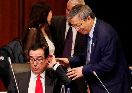 China's Central Bank Governor Yi Gang, right, approaches U.S. Treasury Secretary Steven Mnuchin during the G20 Finance Ministers and Central Bank Governors Meeting, Saturday in Fukuoka, Japan.