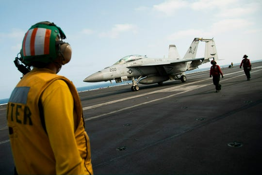 An F/A-18 fighter jet taxis Monday on the deck of the USS Abraham Lincoln aircraft carrier in the Persian Gulf. The USS Abraham Lincoln, with its contingent of Navy destroyers and cruisers and a fighting force of about 70 aircraft, is the centerpiece of the Pentagon's response to what it calls Iranian threats to attack U.S. forces or commercial shipping in the Persian Gulf region.