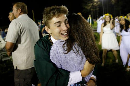 Sean Newsom hugs his mother, Melissa after graduation ceremonies at Paradise High School in Paradise, Calif., Thursday June 6, 2019.