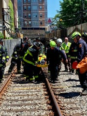 This photo provided by the Boston Fire Department, Firefighters and EMT personnel carry an injured person after a train car derailed in Boston on Saturday, June 8, 2019.