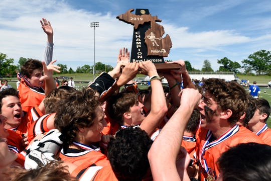 The Birmingham Brother Rice boys lacrosse team members celebrate with the team trophy after a 14-13 victory over Detroit Catholic Central on Saturday in the Division 1 final at Parker Middle School in Howell.