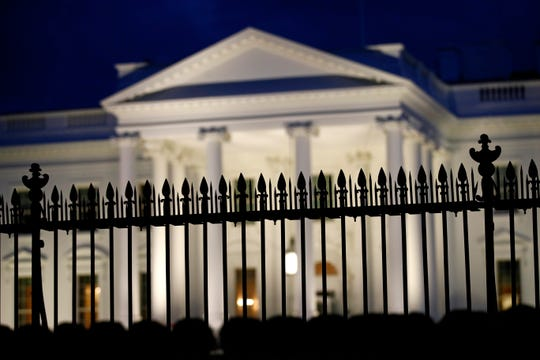 A fence stands in front of the White House at dusk, Thursday, June 6, 2019, in Washington.