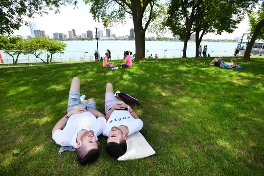 Claudio Martini and Sam Shehedeh relax in the shade along the Detroit River during the Motor City Pride festival.