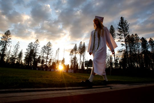 In white cap and gown a graduating senior walks to the graduation ceremonies at Paradise High School in Paradise, Calif., Thursday June 6, 2019.