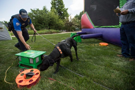 Fort Collins Police Services officer Phillip Selgren and k-9 officer Gunnar search behind inflatable bounce houses during the second day of Taste of Fort Collins on Saturday, June 8, 2019, in Fort Collins, Colo.