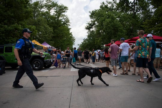 Fort Collins Police Services officer Phillip Selgren and k-9 officer Gunnar work through the crowd during the second day of Taste of Fort Collins on Saturday, June 8, 2019, in Fort Collins, Colo.