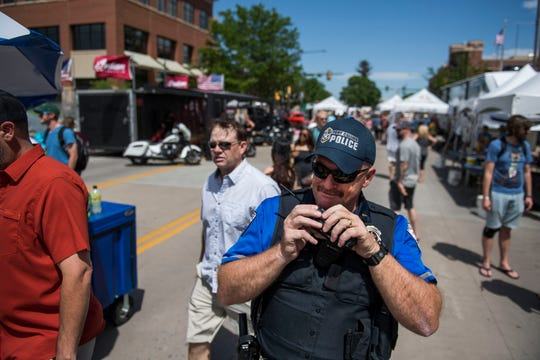 Fort Collins Police Services special events Lt. Jim Byrne calls on his radio to try to find a wheelchair for a festival-goer during the second day of Taste of Fort Collins on Saturday, June 8, 2019, in Fort Collins, Colo.