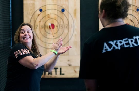 Chandra Cantu celebrates hitting a bull's-eye at TJ's Hatchet Hangout on Friday in Cape Coral. TJ's is the city's first ax-throwing bar.