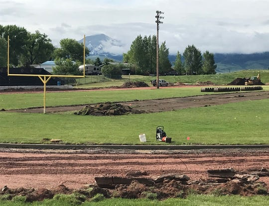 Looking south from the north end of Forzley-Perrine Field in Cascade, new sod (right) will replace the ripped up sod  at center of photo when the new crown is built down the center of the football field. In the lower part of the photo, the work to shave over 90 inches off the old 440-yard track to convert it to 400 meters has been completed.