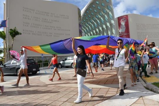 A large pride flag is carried during the third annual Guam Pride March at the Guam Museum in Hagåtña June 8.