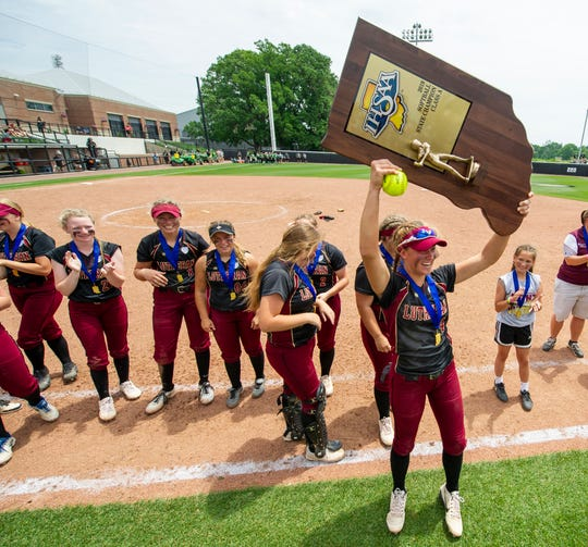 Lutheran High School senior Ryee Morris (4) hoist the trophy over her head to the cheers of the team's fans in the stands. Indianapolis Lutheran High School competed against Pioneer High School, Saturday, June 8, 2019, in the 35th Annual IHSAA Class A Softball State Finals at Bittinger Stadium on the campus of Purdue University in West Lafayette, Ind. Lutheran won the championship 4-1.