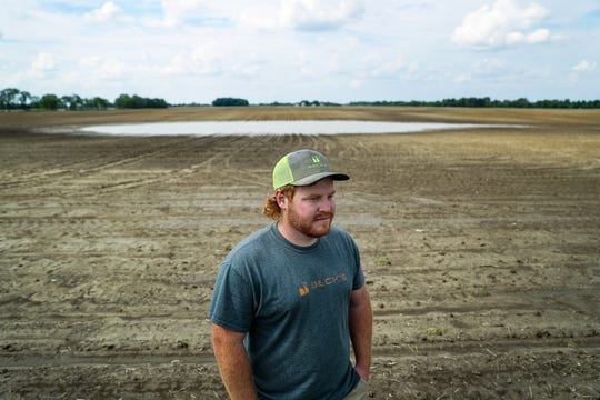 Josh Petry, 29, stands in front of pooled rainwater in the middle of his family's Hancock County farmland in Indiana, Thursday, June 6, 2019.