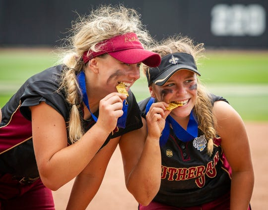 Lutheran High School junior Kayee Gregory (8), left, and junior Gabby Moore (00) pose for photos after their victory. Indianapolis Lutheran High School competed against Pioneer High School, Saturday, June 8, 2019, in the 35th Annual IHSAA Class A Softball State Finals at Bittinger Stadium on the campus of Purdue University in West Lafayette, Ind. Lutheran won the championship 4-1.