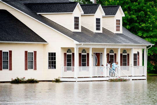 "A family peers at the flood water levels from their porch on the corner of Locust Dr. and Old Middlesboro Hwy. in LaFollette, Tennessee on Saturday, June 8, 2019. According to the NWS, Sunday has the potential for the ""most concentrated period for steadier rainfall,"" which could lead to flooding in low-lying areas."