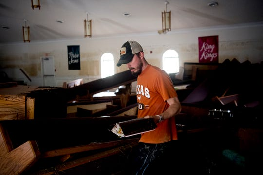 Lukus Alderman, whose father in law is the pastor of Faith Way Assembly of God, discovers his water-damaged Bible among the debris and piled up pews in the sanctuary after a flash flood damaged much of the building overnight on Saturday.