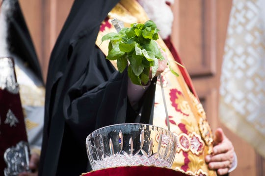 Archbishop Alexios, who oversees the United States' southeast Greek Orthodox churches, dips basil leaves into holy water to bless St. George Greek Orthodox Church.