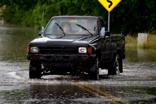 "A vehicle drives through flood waters on the corner of Locust Dr. and Old Middlesboro Hwy. in LaFollette, Tennessee on Saturday. According to the NWS, Sunday has the potential for the ""most concentrated period for steadier rainfall,"" which could lead to flooding in low-lying areas."