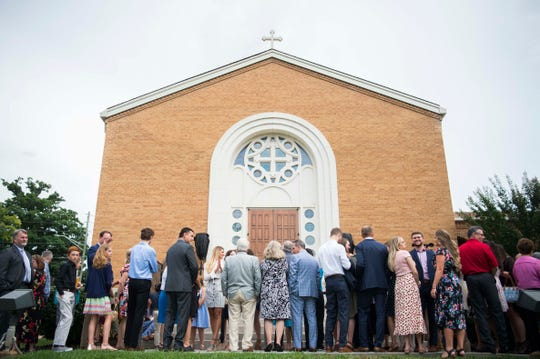 Attendees stand outside St. George Greek Orthodox Church before a door opening event on Saturday. Four years ago, a fire devastated the church.