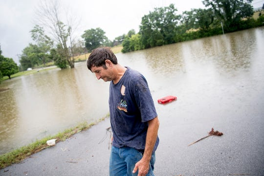 Albert Hatfield, who lives nearby, takes a look at the flood waters on the corner of Locust Dr. and Old Middlesboro Hwy. in LaFollette, Tennessee on Saturday.