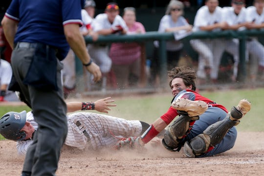 Rossville catcher Corbin Beard (11) reaches out to attempt to tag out Washington Township short stop Bryce Malamatos (12) during the fifth inning of the IHSAA Semi-State baseball game, Saturday, June 8, 2019, at Centennial Park in Plymouth. Washington Township won, 13-8.