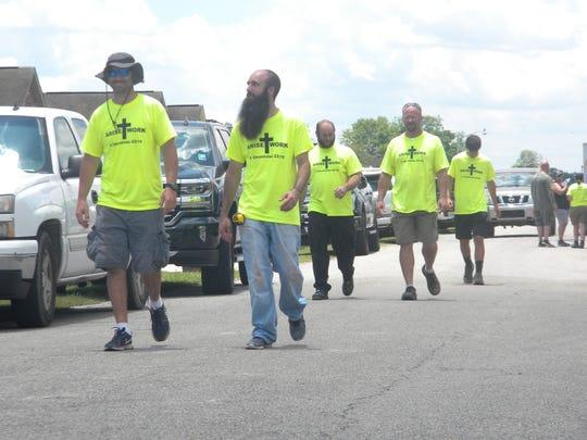 Volunteers walk towards flooded homes to clean