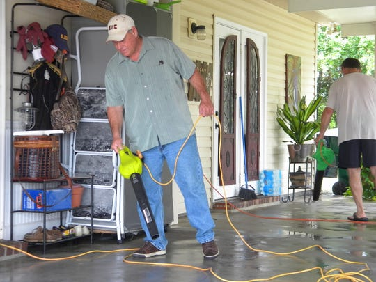 Church group volunteer Josh Garett drying all the water from a flooded garage.