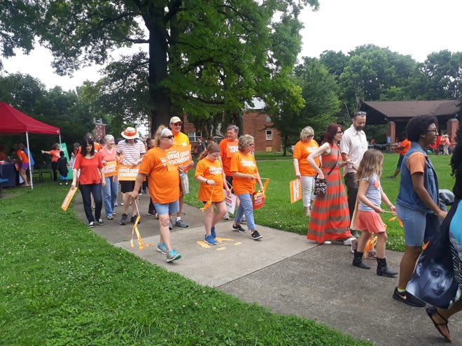 Community members walk in orange at a Moms Demand Action Wear Orange event at Sheppard Park in Louisville, Ky. on June 8, 2019.