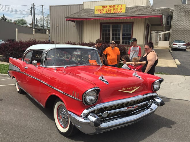 People admire a 1957 Chevrolet Bel Air owned by Gail Potter at Saturday's Cruisin' with the Cops car show in Bucyrus.