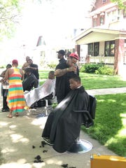 Three barbers volunteered to give free haircuts on the sidewalk during the block party.
