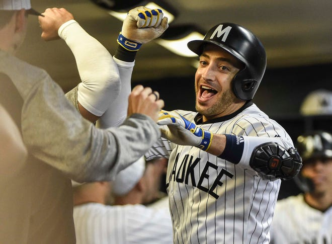 Ryan Braun is a happy camper as he's congratulated by teammates in the Brewers dugout after blasting a three-run homer against the Pirates in the sixth inning.