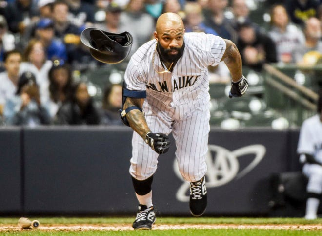 Eric Thames of the Brewers loses his helmet as he busts out of the batter's box in a futile attempt to beat out a grounder against the Pirates.