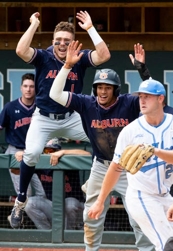 Auburn's Judd Ward (1) and Will Holland, center, celebrate behind North Carolina's Hansen Butler (24) as Auburn takes the lead over North Carolina during Game 1 at the NCAA college baseball super regional tournament in Chapel Hill, N.C., Saturday, Jun 8, 2019. (AP Photo/Ben McKeown)