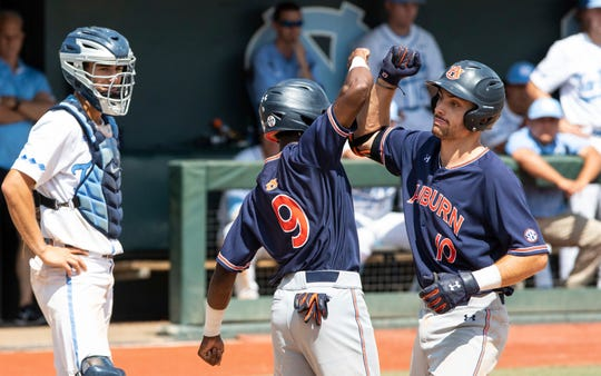 Auburn's Edouard Julien (10) celebrates with teammate Ryan Bliss (9) after hitting a home run during the ninth inning in Game 1 at the NCAA college baseball super regional tournament in Chapel Hill, N.C., Saturday, Jun 8, 2019. (AP Photo/Ben McKeown)