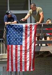 Gabe Henderson and Derrick Kepler hang a flag that covered the casket of their friend Richard O. Quill III at the lake house where he grew up on Old Hickory Lake on Friday, May 24, 2019.