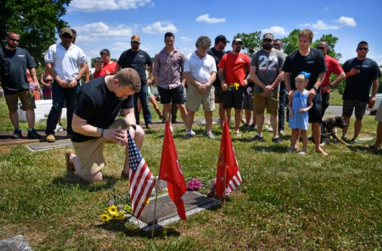 Nick Darrah kneels at the grave of his fellow Marine Richard O. Quill III. About 50 Marines who were assigned to Golf Company, 2nd Battalion, 4th Marine division and served in Iraq together in 2004 came to Nashville to remember Quill with fellowship over the Memorial Day weekend.