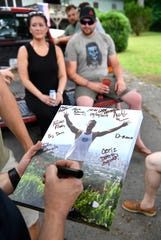 Marines sign a photo of Richard O. Quill III as they come together to remember their fallen comrade May 24, 2019.