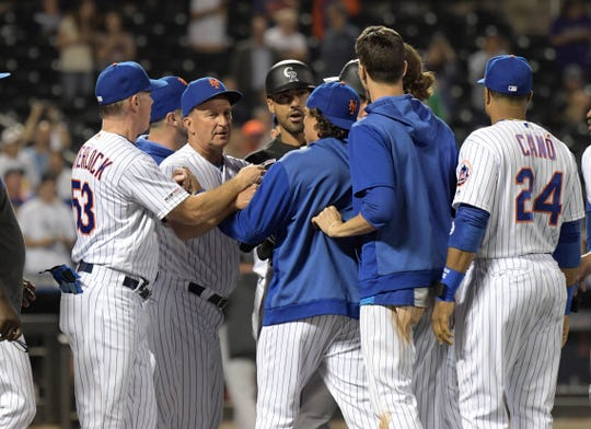 New York Mets and Colorado Rockies players and coaches confront each other on the field after Mets pitcher Drew Gagnon hit Rockies batter Ian Desmond with a pitch during the eighth inning of a baseball game Friday, June 7, 2019, in New York.