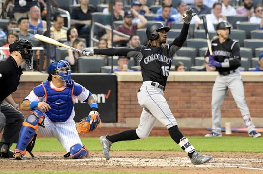Colorado Rockies' Raimel Tapia (15) follows through on an RBI double during the third inning of a baseball game as New York Mets catcher Wilson Ramos and home plate umpire Chris Segal watch Friday, June 7, 2019, in New York.