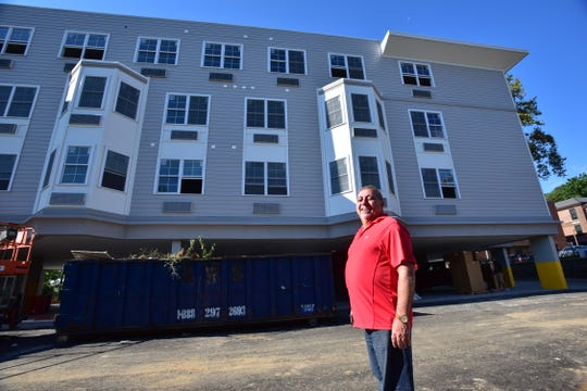 Fred Daibes, a local developer in Edgewater, poses for a photo by an affordable housing building on Winterburn Place in Edgewater.