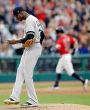 New York Yankees starting pitcher Domingo German, left, waits for Cleveland Indians' Tyler Naquin to run the bases on a solo home run during the fifth inning in a game Friday June 7, 2019, in Cleveland.