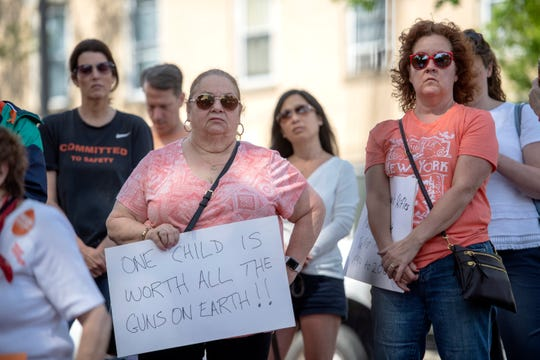 (left) Pat Henry, of Hackensack, holds a sign during a Gun Violence Awareness Rally in Ridgewood on Saturday, June 8, 2019. (right) Margaret Durveck, of Hackensack.