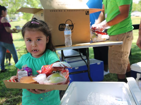 Santiana Sanchez, 3, smiles after receiving her free lunch at Young Park, Saturday June 8, 2019.