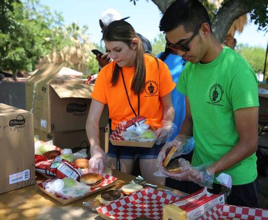 Elisia Staton and Mitchell Allred prepare lunches for kids at Young Park, during the Families and Youth Inc. summer food kickoff event, Saturday, June 8, 2019.