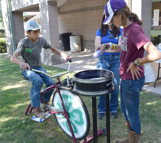 Kayla Higgins of Valencia County drizzles paint on her T-shirt design while Santiago Casaus of Sandoval County pedals the stationary bicycle to create centrifugal force that spreads the paint. The activity was part of the New Mexico State University 4-H Horse School. June 3, 2019.