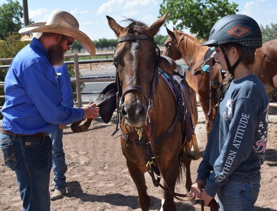 Riding instructor John Allen checks the bridle on a horse prior to Theresa Cardiel of Otero County entering the riding ring at the New Mexico State University 4-H Horse School, June 3-6, 2019.