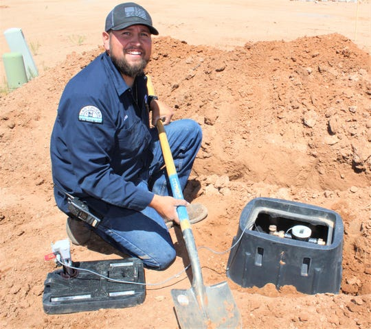 LCU Water senior maintenance worker Andres Serna installs an LCU water meter box at a construction site on Big Jim Drive off Holman Road. Water meters at new homes will have emergency shut-off valves on the outside of the meter box.