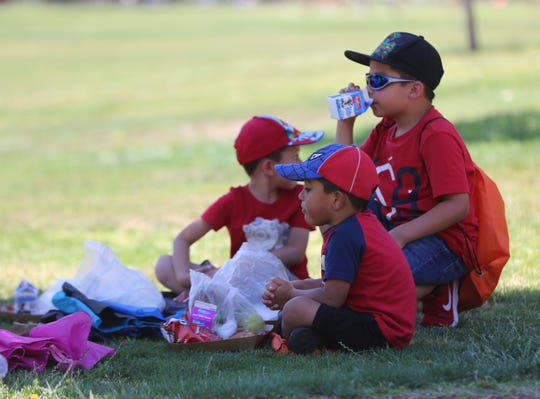 Damian Castaneda, 7, Carlos Murguia 6, and Cayden Murgia 4, enjoy a free lunch at Young Park, during the Families and Youth Inc., summer food kickoff event, Saturday June 8, 2019.