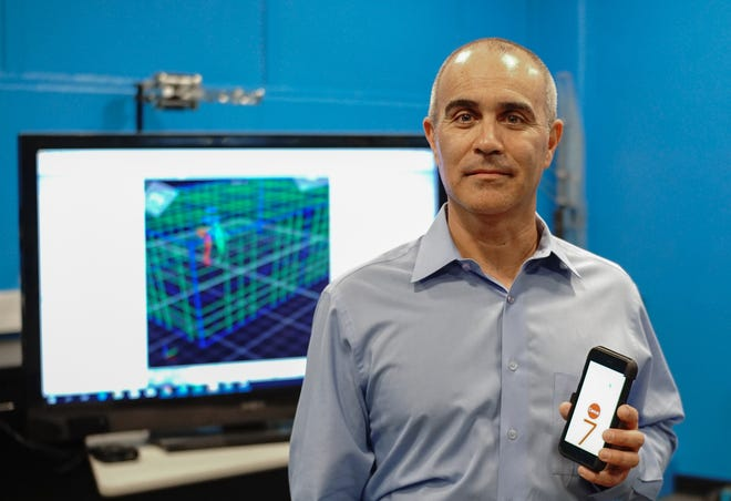 NMSU College of Engineering Research Dean Phillip De Leon shows the phone app he created to help determine the risk of falls. Behind him is an image from a motion capture system used to verify the data collected by the app.